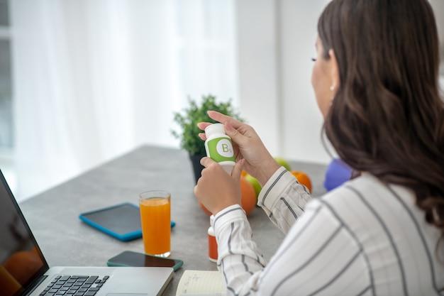 Mulher com uma blusa listrada segurando um frasco de vitaminas