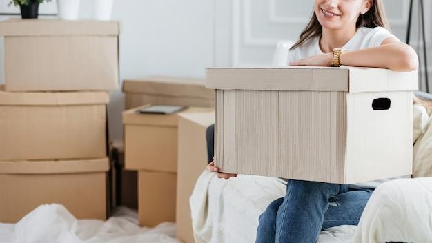 Mulher com uma caixa de papelão sentada no sofá