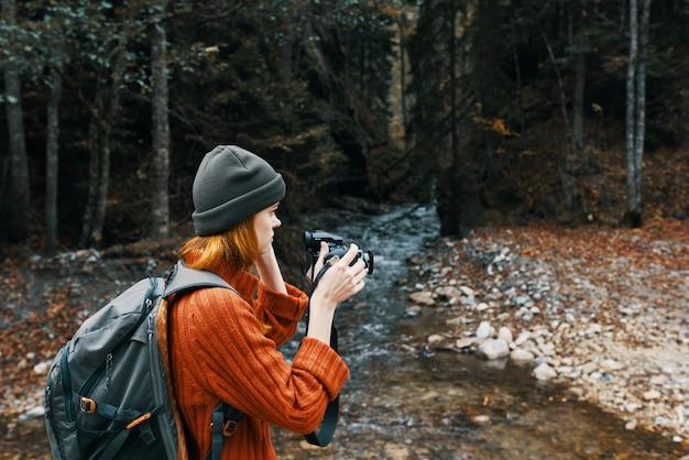 Mulher com uma câmera na natureza nas montanhas perto do rio e paisagem de floresta com árvores altas Foto Premium