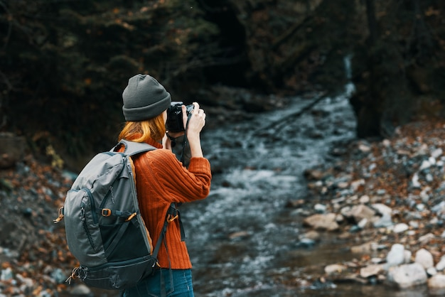 Mulher com uma câmera na natureza nas montanhas perto do rio e paisagem de floresta com árvores altas