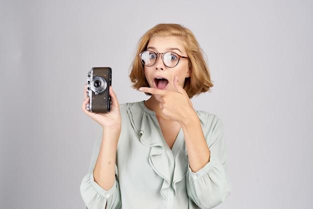 Mulher com uma câmera nas mãos e em um modelo de emoções de vista frontal de camisa clara.