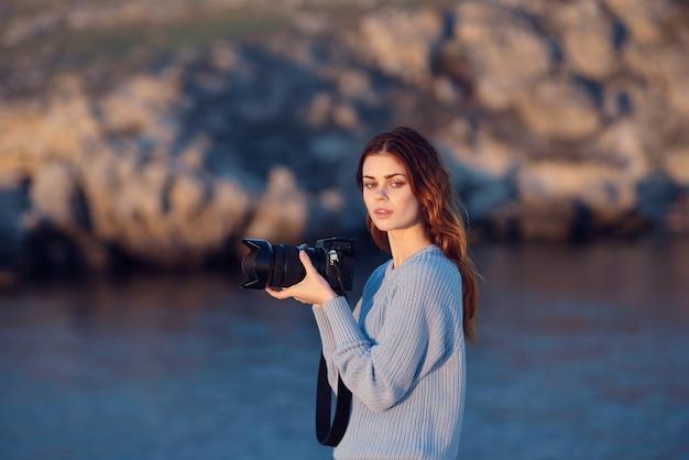 Mulher com uma câmera nas mãos fotografia profissional montanha rochosa viajar