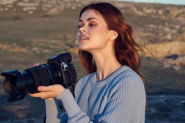 Mulher com uma câmera nas mãos viagens de passatempo ao ar livre nas montanhas rochosas