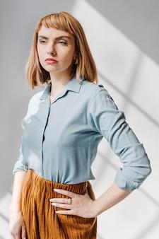 Mulher com uma camisa azul perto da parede branca