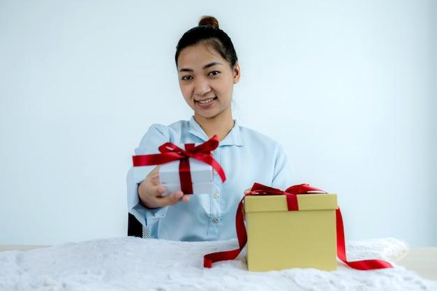 Mulher com uma camisa azul segurando uma caixa de presente branca amarrada com uma fita vermelha presente para o festival de dar feriados especiais como natal, dia dos namorados