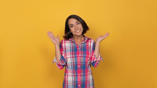 Mulher com uma camisa xadrez na parede amarela