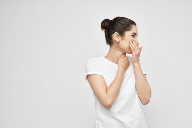 Mulher com uma camiseta branca com dor no pescoço luz de fundo