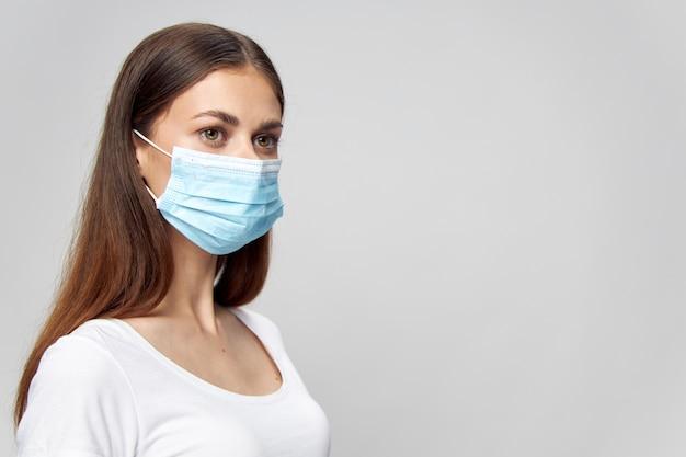 Mulher com uma camiseta branca e uma máscara médica