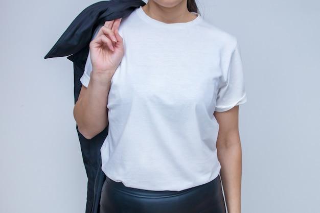 Mulher com uma camiseta branca para inscrições simuladas com um casaco na mão