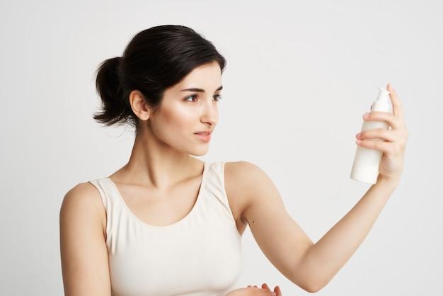 Mulher com uma camiseta branca sentada com as mãos hidratando os cuidados com a pele