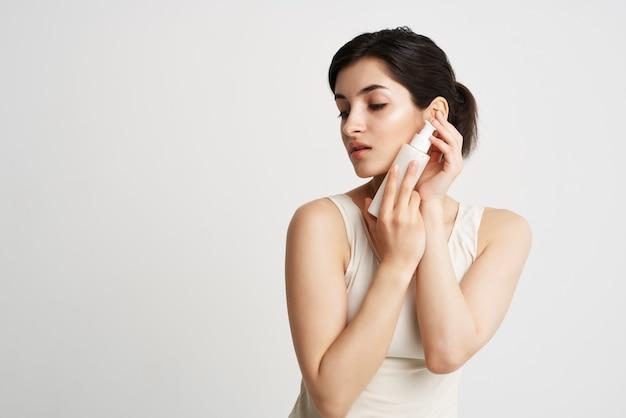 Mulher com uma camiseta branca sentou-se com as mãos, hidratando os cuidados com a pele. foto de alta qualidade