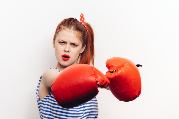 Mulher com uma camiseta e luvas de boxe vermelhas pratica esportes com um fundo claro