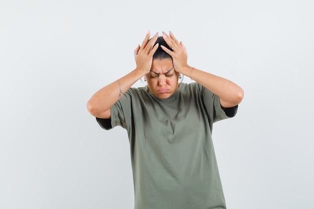 Mulher com uma camiseta segurando as mãos na cabeça e parecendo triste