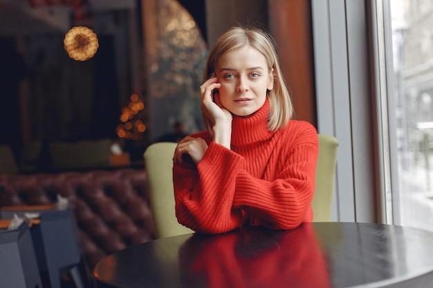 Mulher com uma camisola vermelha. senhora em um restaurante.