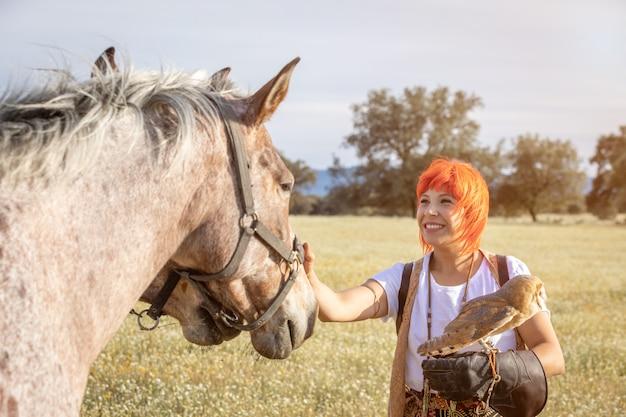 Mulher com uma coruja branca no braço e perto de cavalos