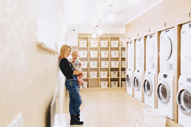 Mulher com uma criança nas mãos na lavanderia está à espera de roupas