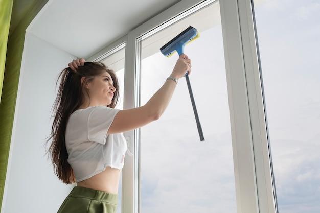 Mulher com uma emoção insatisfeita sacode a janela da terra, olhando para o céu. mulher limpando janela em casa