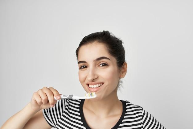Mulher com uma escova de dentes de camiseta listrada na mão isolado fundo