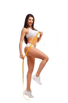 Mulher com uma fita métrica e uma perna levantada