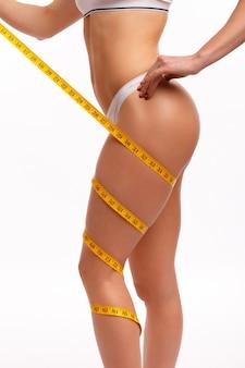 Mulher com uma fita métrica enrolada em sua perna
