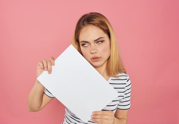 Mulher com uma folha de papel branca em uma maquete de publicidade rosa