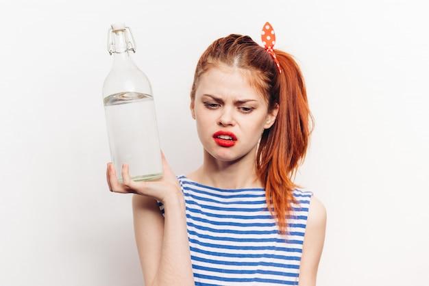Mulher com uma garrafa de álcool nas mãos dela
