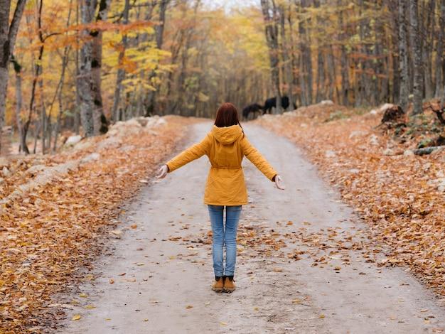 Mulher com uma jaqueta amarela caminhando ao ar livre da floresta de outono