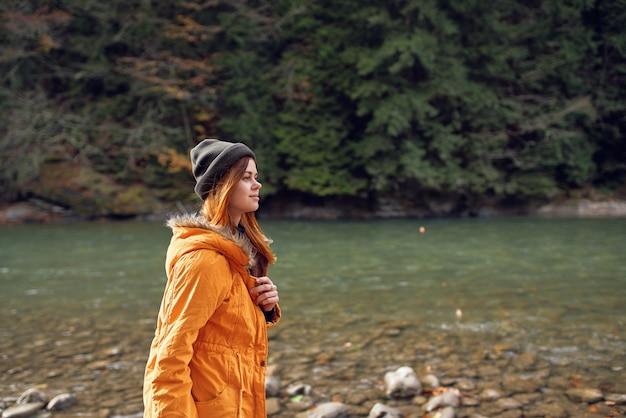 Mulher com uma jaqueta amarela perto do passeio pela natureza nas montanhas do rio