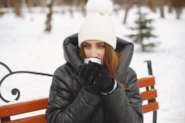Mulher com uma jaqueta preta bebendo chá ao ar livre