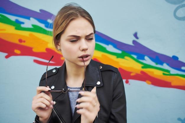 Mulher com uma jaqueta preta com óculos na parede multicolorida da rua posando