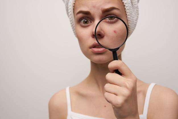 Mulher com uma lupa na mão, close-up de problemas de pele