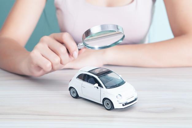 Mulher com uma lupa olha para o carro. conceito de busca de carro