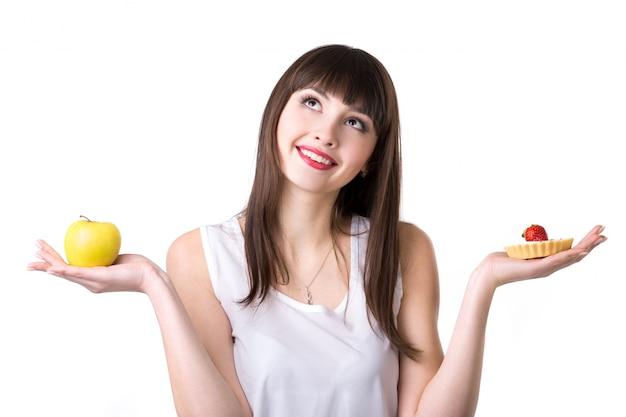 Mulher com uma maçã em uma mão e um bolo na outra