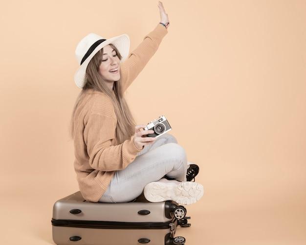 Mulher com uma mala e um chapéu, câmara fotográfica
