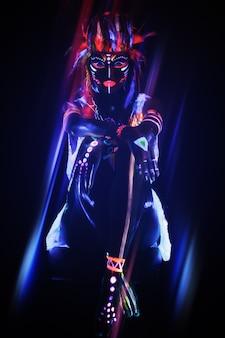 Mulher com uma maquiagem de néon na luz ultravioleta