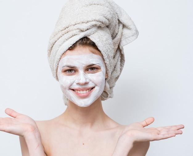 Mulher com uma máscara branca contra pontos pretos no rosto e uma toalha na cabeça