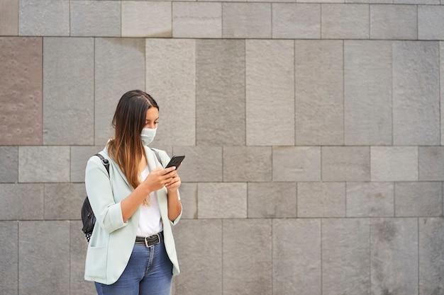 Mulher com uma máscara de escrita com um smartphone.