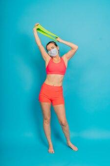Mulher com uma máscara de proteção facial e roupas de ginástica isoladas sobre fundo azul.