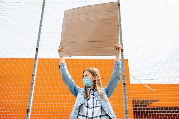 Mulher com uma máscara de proteção médica segura um cartaz de papelão vazio para uma cópia do espaço, de pé em uma rua da cidade contra uma parede amarela