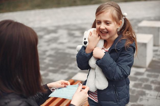 Mulher com uma máscara descartável está ensinando seu filho a usar um respirador