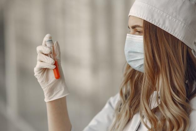 Mulher com uma máscara e uniforme segurando um tubo nas mãos