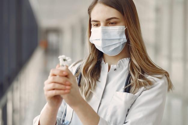 Mulher com uma máscara e uniforme segurando uma flor nas mãos