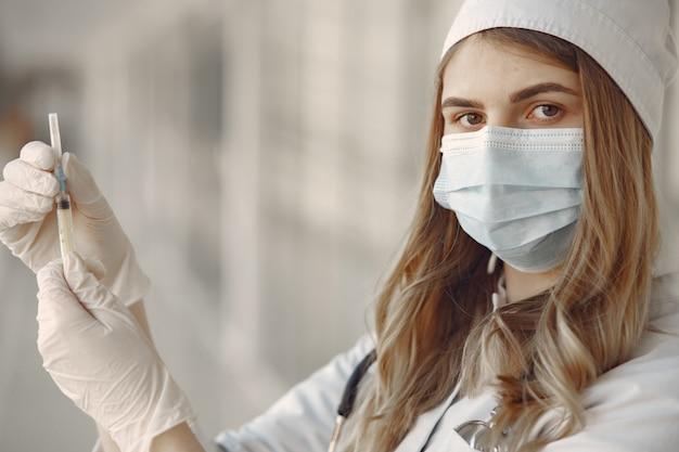 Mulher com uma máscara e uniforme segurando uma seringa nas mãos