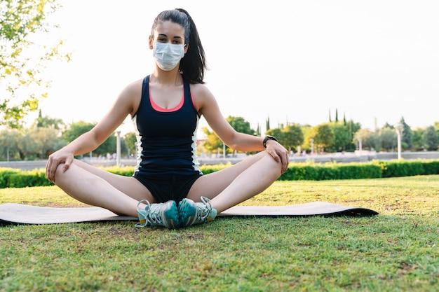 Mulher com uma máscara fazendo a posição de ioga de lótus em um parque público