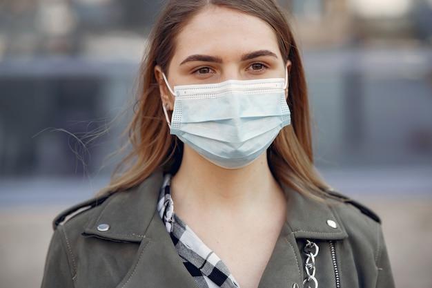 Mulher com uma máscara fica na rua