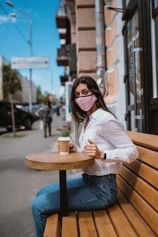 Mulher com uma máscara médica bebe café na rua
