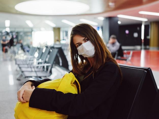 Mulher com uma máscara médica com uma mochila amarela sentada no aeroporto esperando