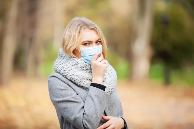 Mulher com uma máscara médica na floresta de outono
