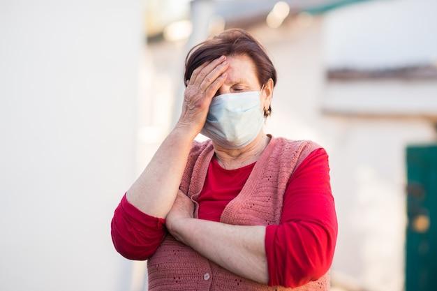 Mulher com uma máscara médica segurando sua cabeça.