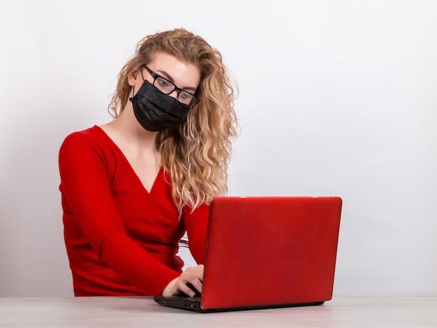Mulher com uma máscara médica, trabalhando remotamente no computador em branco.